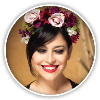 A circular closeup portrait of the designer wearing flowers on her hair
