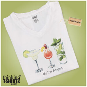 """A folded white v-neck t-shirt with an illustration on chest area consisted of three different drinks. The garment is viewed on a green background. The inscription reads; """"My Tres Amigos."""""""